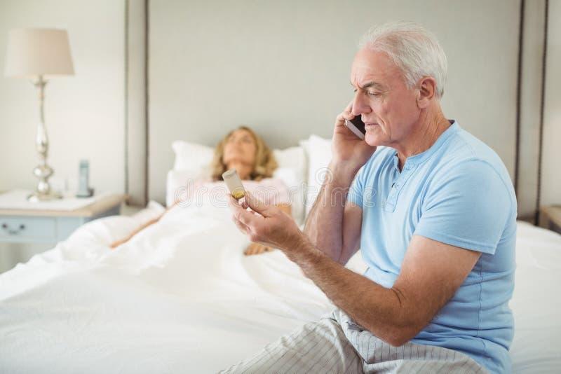 Älterer Mann, der am Handy während ältere Frau stillsteht im Schlafzimmer spricht stockfoto