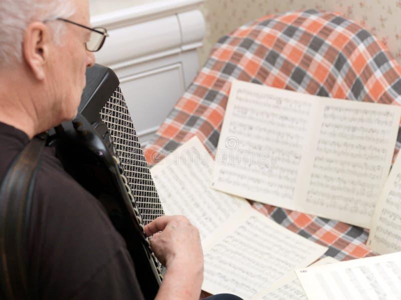 Älterer Mann, der Harmonika spielt stockfotografie
