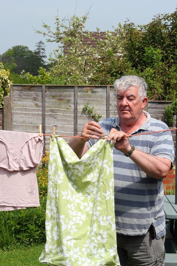 Älterer Mann, der heraus die Reinigung hängt. stockfoto