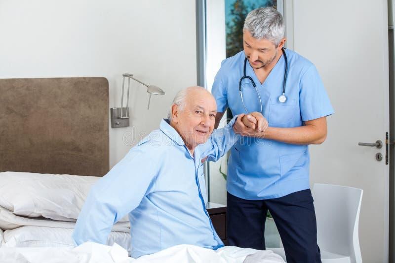 Älterer Mann, der herein vom männlichen Wärter unterstützt wird lizenzfreie stockbilder