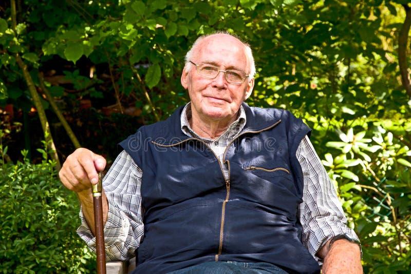 Älterer Mann, der im Garten sitzt stockfotografie