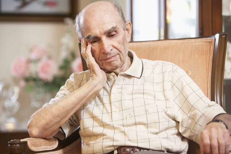 Älterer Mann, der im Lehnsessel stillsteht lizenzfreies stockfoto
