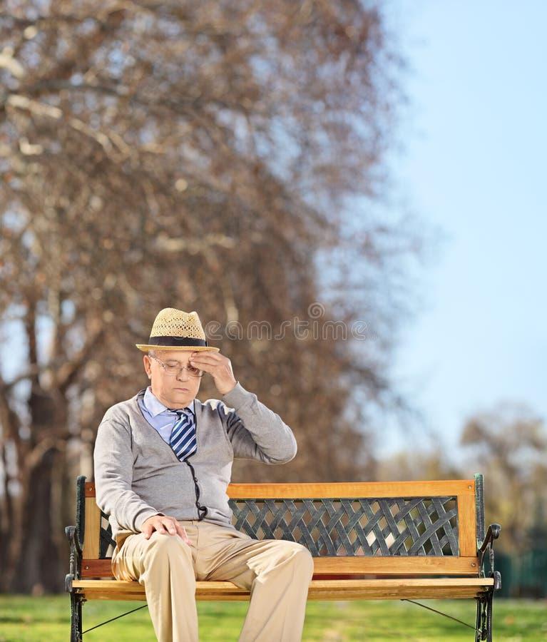 Älterer Mann, der im Park sitzt und Kopfschmerzen hat stockbild