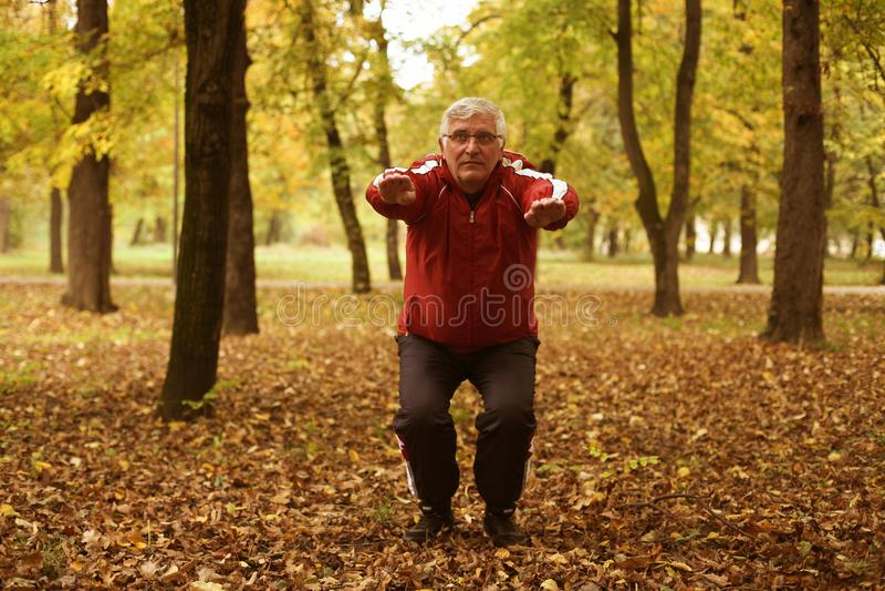 Älterer Mann, der im Park trainiert stockfotos