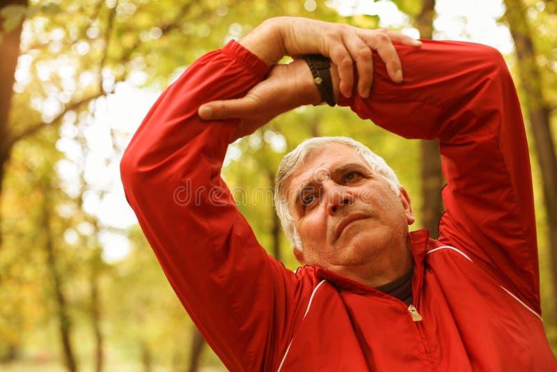 Älterer Mann, der im Park trainiert lizenzfreie stockbilder