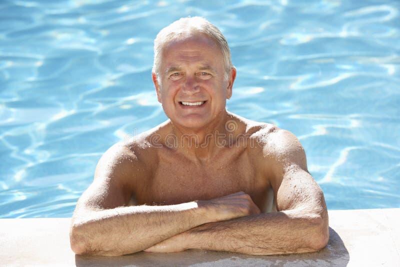Älterer Mann, der im Swimmingpool sich entspannt stockfotos