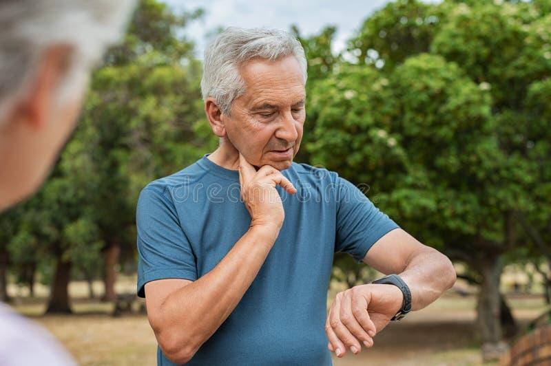 Älterer Mann, der Impuls nachdem dem Laufen überprüft stockbilder