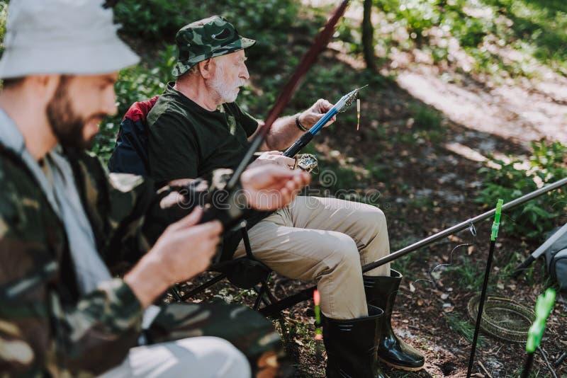 Älterer Mann, der Köder auf den Haken bei der Fischerei setzt stockbilder