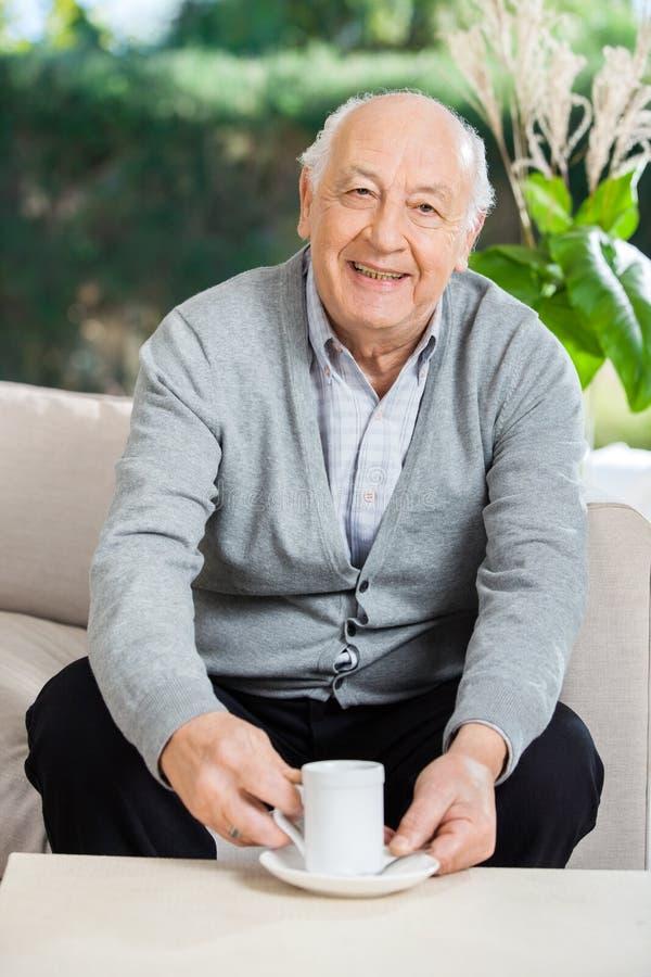 Älterer Mann, der Kaffee am Pflegeheim-Portal trinkt stockbilder