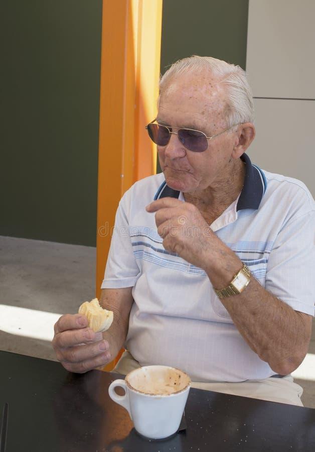 Älterer Mann, der Kaffee und Keks genießt stockfotografie