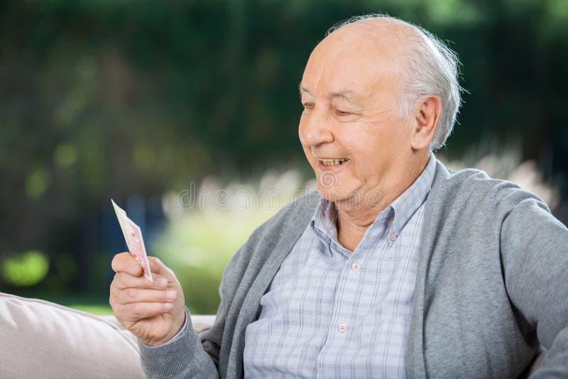 Älterer Mann, der Karten beim Sitzen auf Couch betrachtet lizenzfreie stockfotografie