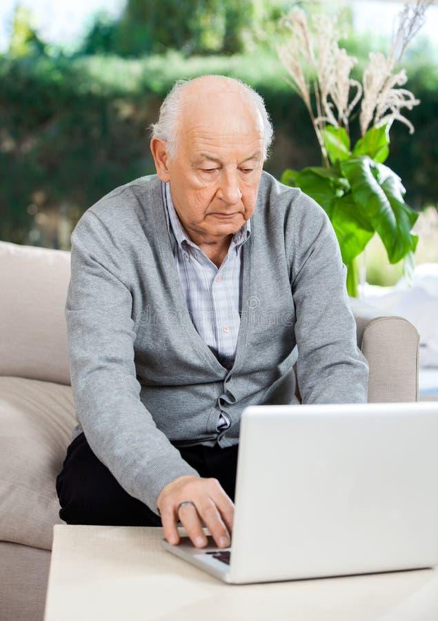 Älterer Mann, der Laptop am Pflegeheim-Portal verwendet lizenzfreie stockbilder