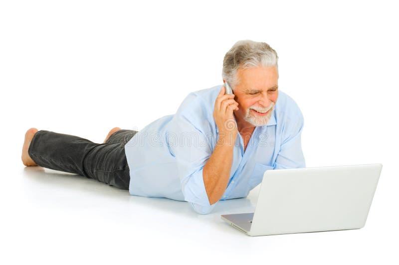 Älterer Mann, der Laptop und Mobile verwendet stockfotografie