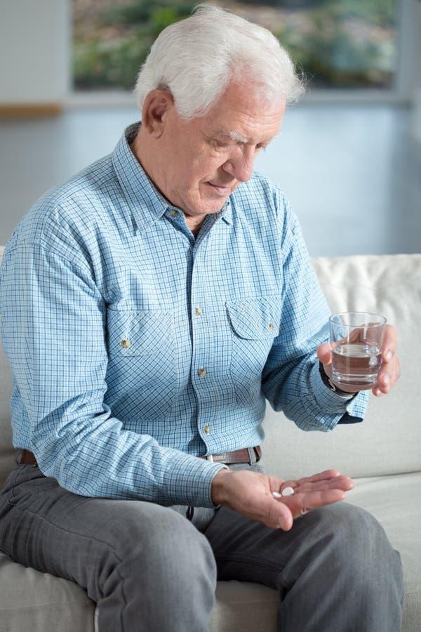 Älterer Mann, der Medikament nimmt stockbild