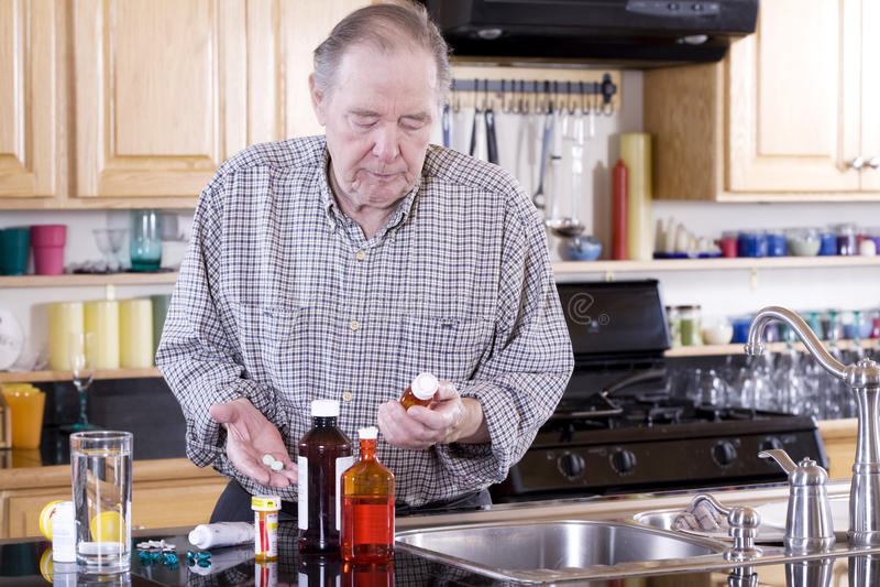 Älterer Mann, der Medizin nimmt stockbilder