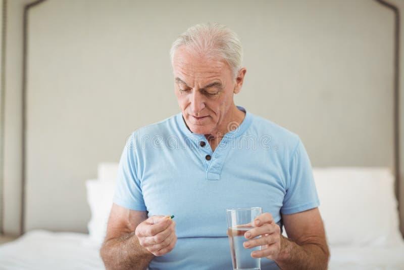 Älterer Mann, der Medizin und Glas Wasser hält lizenzfreie stockfotografie