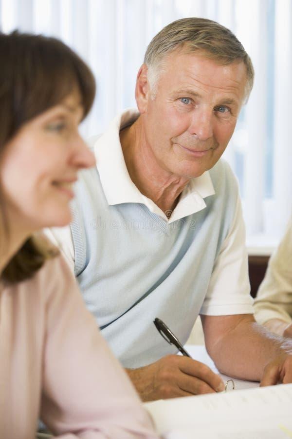 Älterer Mann, der mit anderen Kursteilnehmern studiert lizenzfreie stockbilder