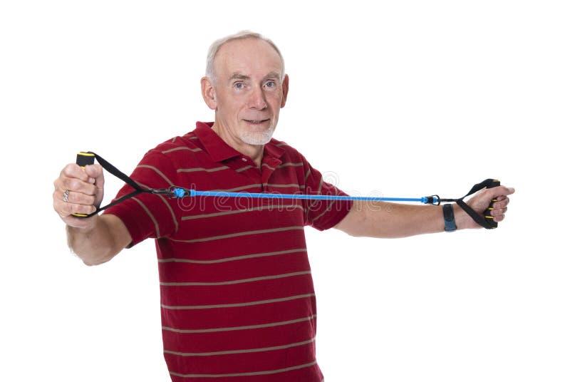 Älterer Mann, der mit Ausdehnungsband trainiert stockfoto