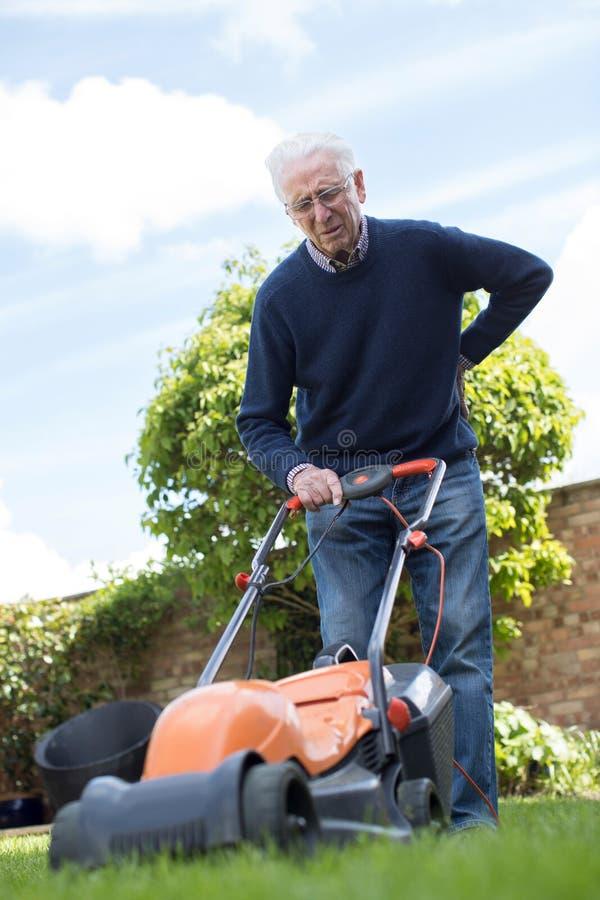 Älterer Mann, der mit Rückenschmerzen leidet, während, elektrischen Rasen MO verwendend lizenzfreie stockfotografie