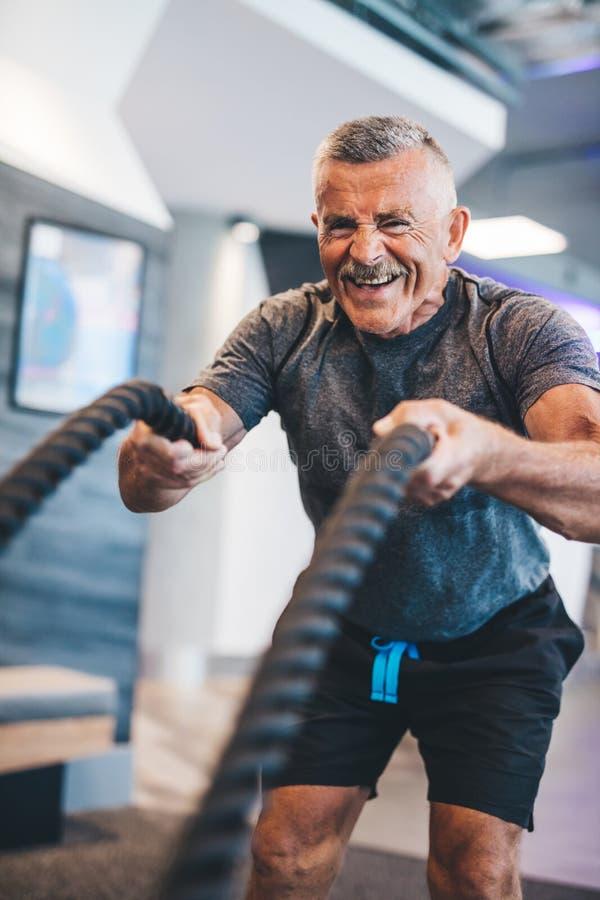 Älterer Mann, der mit Seilen an der Turnhalle trainiert lizenzfreies stockbild