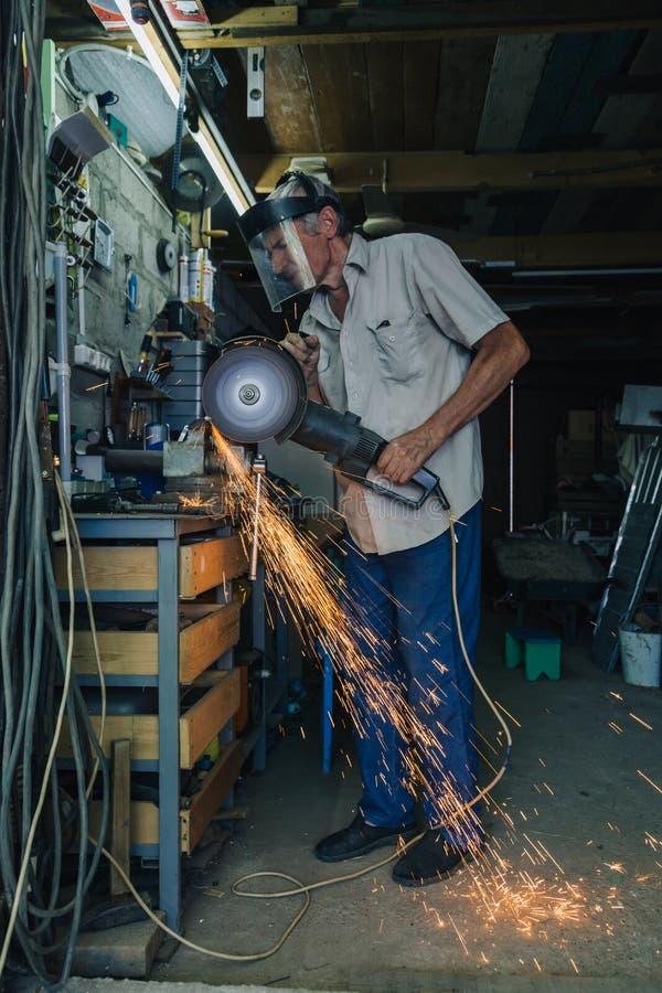 Älterer Mann, der mit Winkelschleifer arbeitet stockfotos