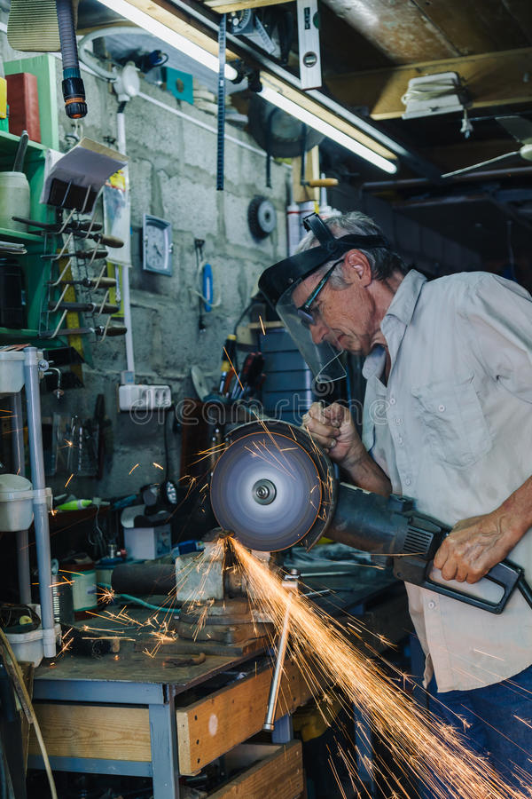 Älterer Mann, der mit Winkelschleifer arbeitet lizenzfreies stockfoto