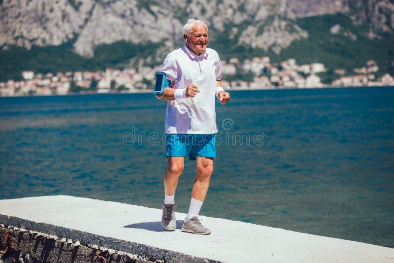 Älterer Mann, der Morgenübung am Strand tut stockfotos