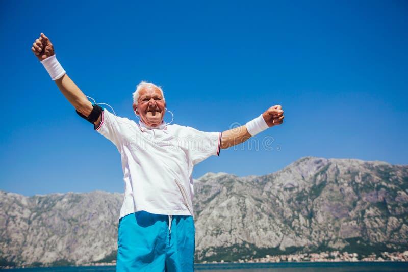 Älterer Mann, der Morgenübung am Strand tut lizenzfreie stockfotografie