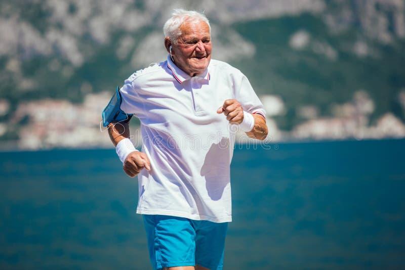 Älterer Mann, der Morgenübung am Strand tut lizenzfreies stockfoto