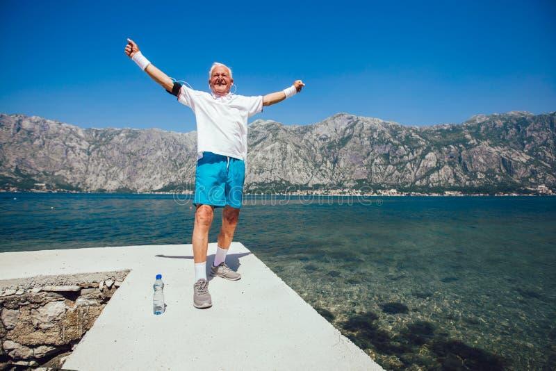 Älterer Mann, der Morgenübung am Strand tut stockfotografie