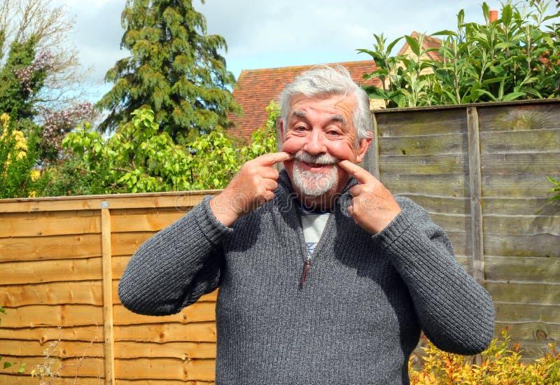 Älterer Mann, der Mund in ein Lächeln zieht lizenzfreie stockfotos