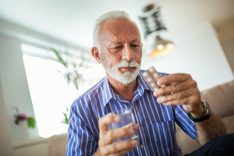 Älterer Mann, der Pillen einnimmt lizenzfreies stockfoto