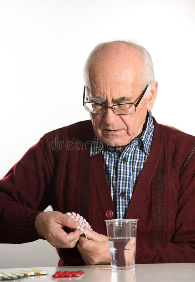 Älterer Mann, der Pillen einnimmt stockfotografie
