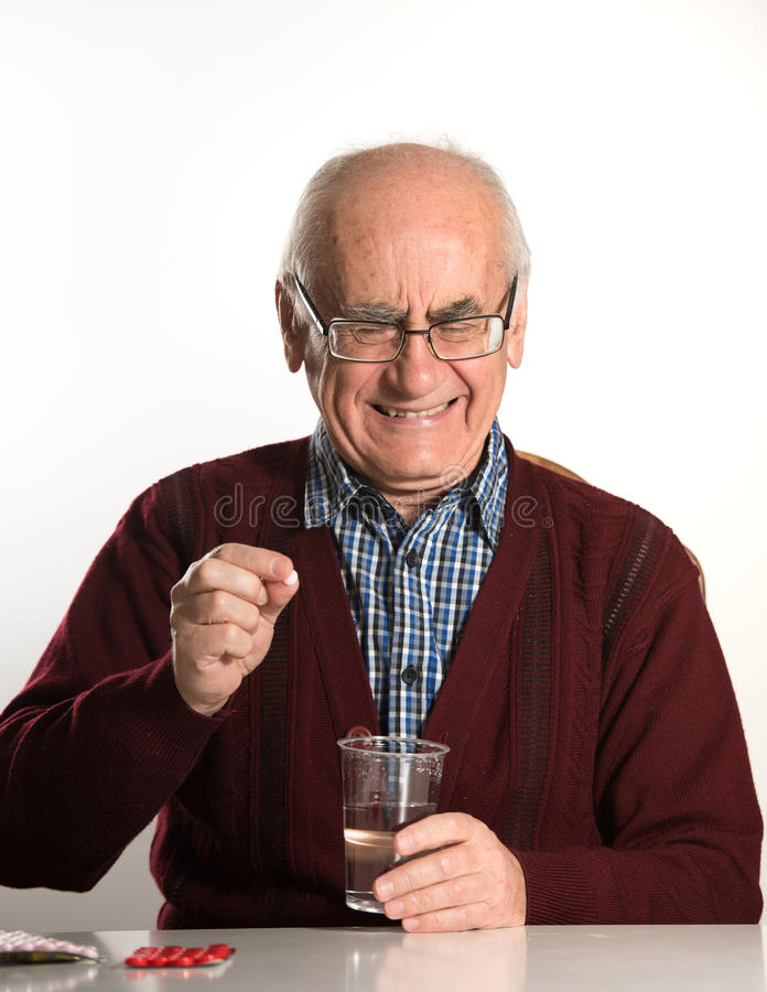 Älterer Mann, der Pillen einnimmt stockfoto