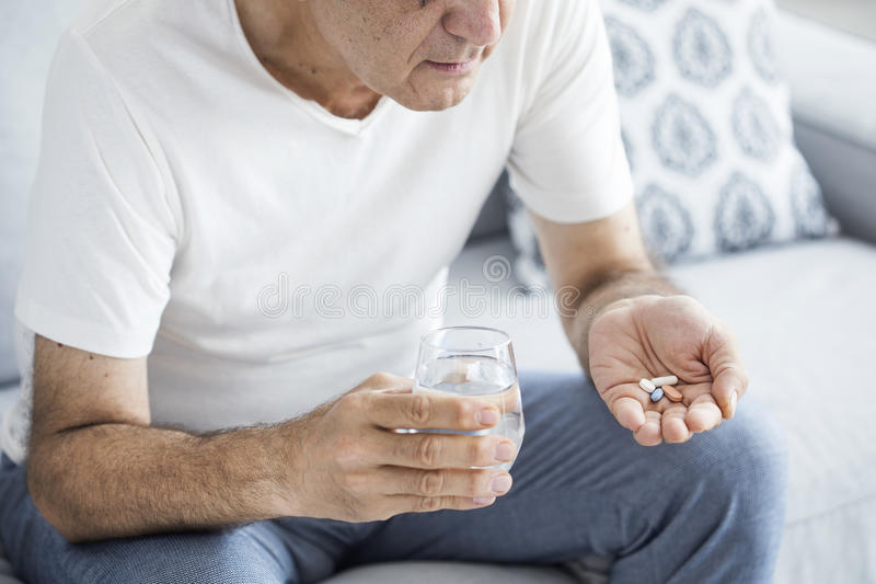 Älterer Mann, der Pillen einnimmt stockbilder