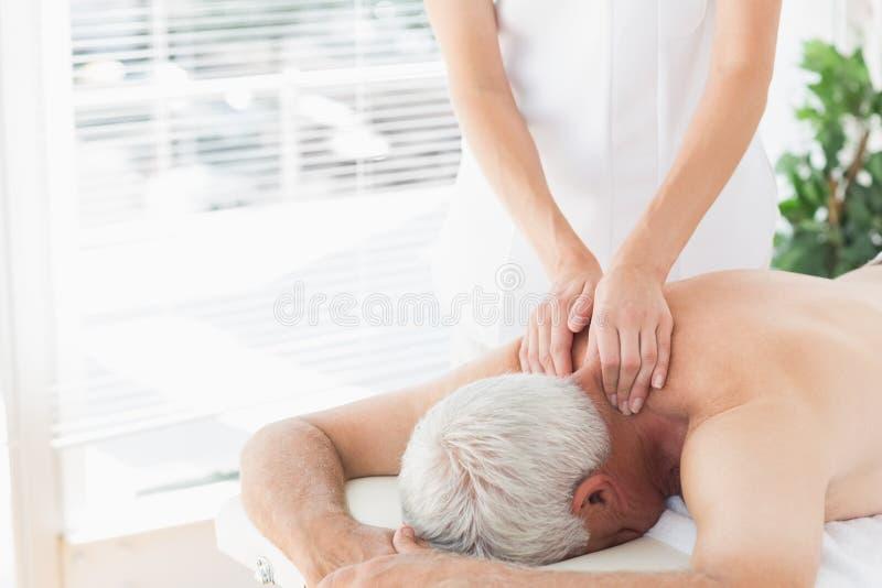 Älterer Mann, der Rückenmassage erhält lizenzfreies stockbild