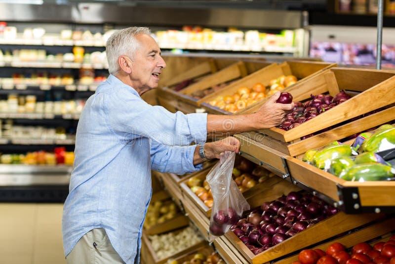 Älterer Mann, der rote Zwiebel kauft lizenzfreie stockfotos