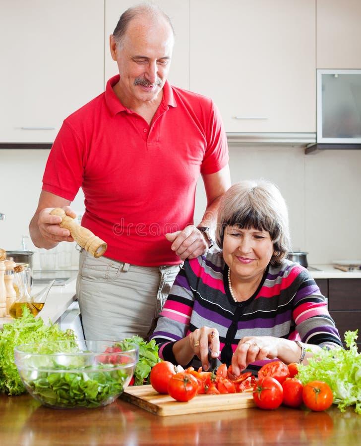 Älterer Mann in der roten und reifen Frau, die das Mittagessen kocht lizenzfreies stockfoto