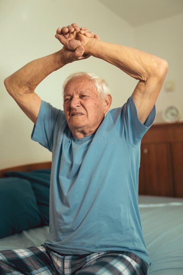 Älterer Mann, der in Schlafzimmer ausdehnt stockbild