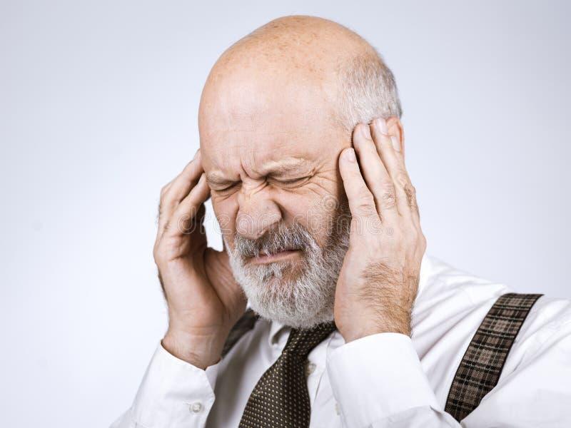 Älterer Mann, der schlimmen Kopfschmerzen hat stockfotos
