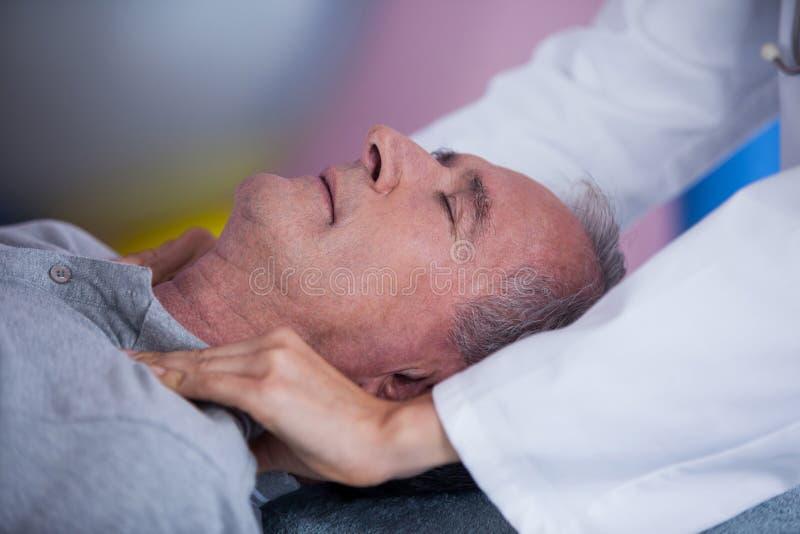 Älterer Mann, der Schultermassage vom Physiotherapeuten empfängt stockbild