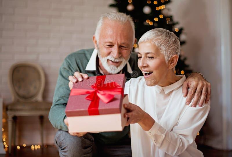 Älterer Mann, der seiner Frau ein Weihnachtsgeschenk gibt stockfoto