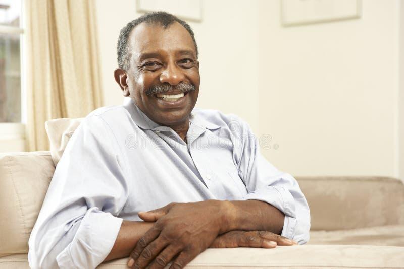 Älterer Mann, der sich zu Hause im Stuhl entspannt stockfotos
