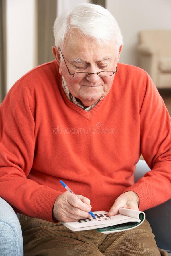 Älterer Mann, der sich zu Hause im Stuhl entspannt lizenzfreie stockbilder