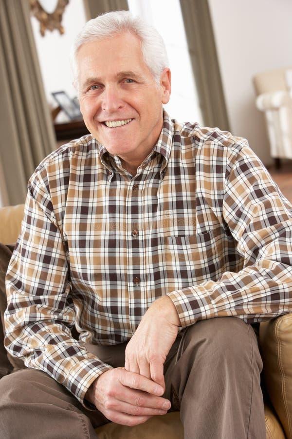 Älterer Mann, der sich zu Hause im Stuhl entspannt lizenzfreies stockfoto