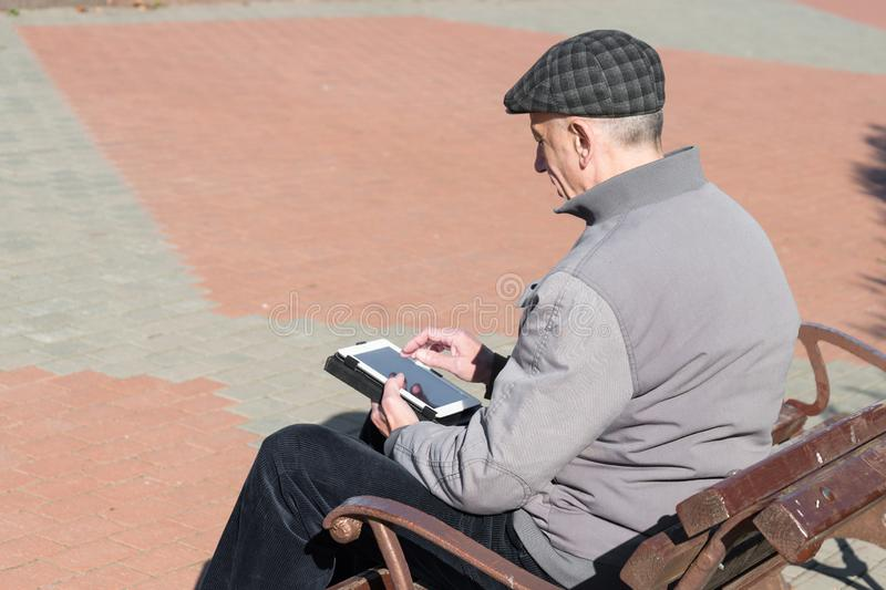 Älterer älterer Mann, der Tablet-Computer verwendet lizenzfreie stockfotos