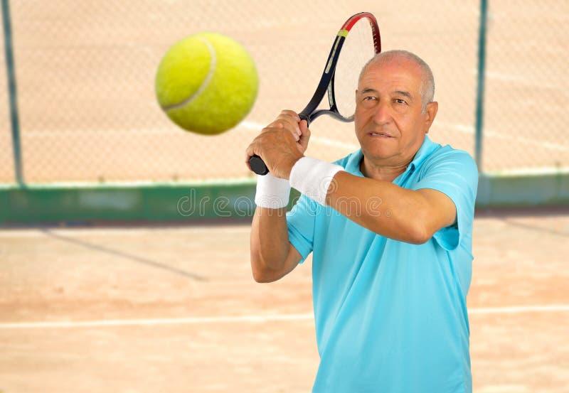 Älterer Mann, der Tennis spielt lizenzfreie stockbilder