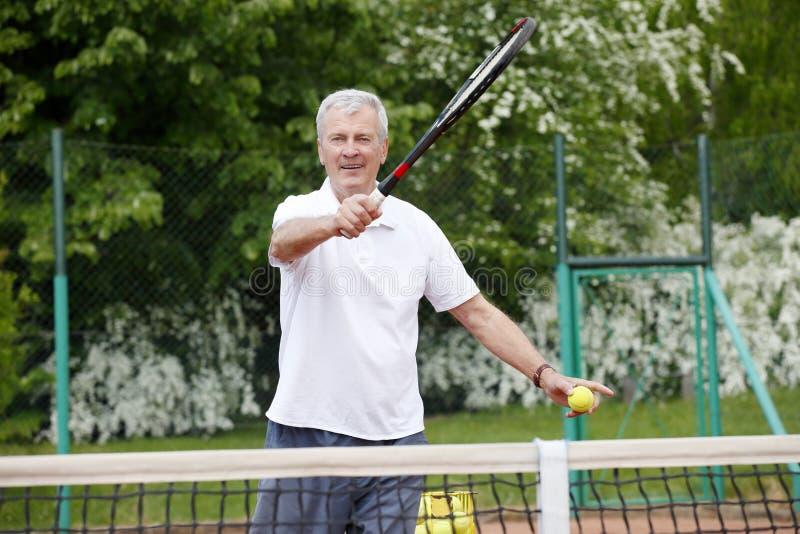 Älterer Mann, der Tennis spielt lizenzfreie stockfotografie