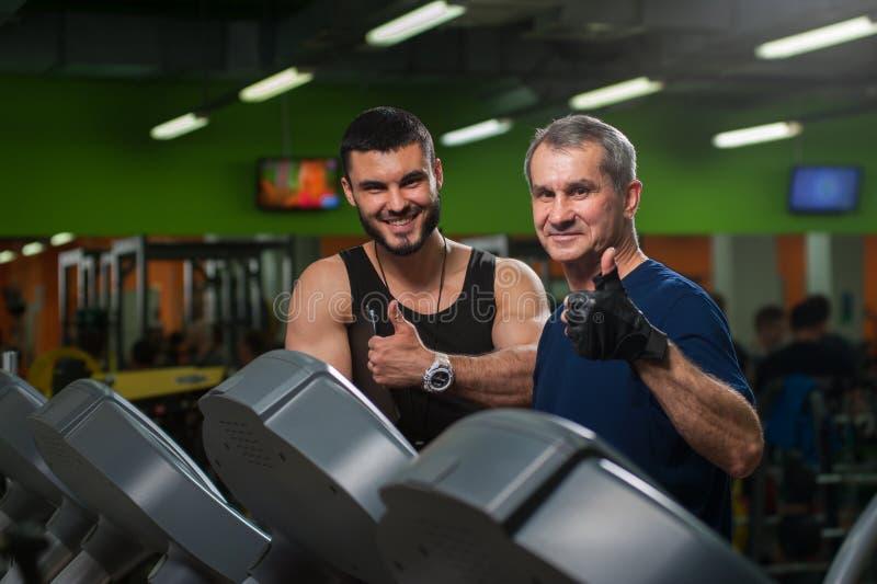 Älterer Mann, der an Tretmühle mit Trainer arbeitet lizenzfreie stockbilder