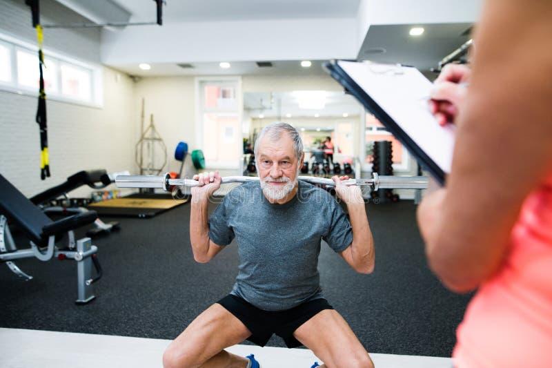 Älterer Mann in der Turnhalle ausarbeitend mit Gewichten lizenzfreie stockbilder